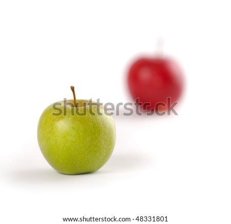 Green apple in focus and red apple out of focus isolated on white background