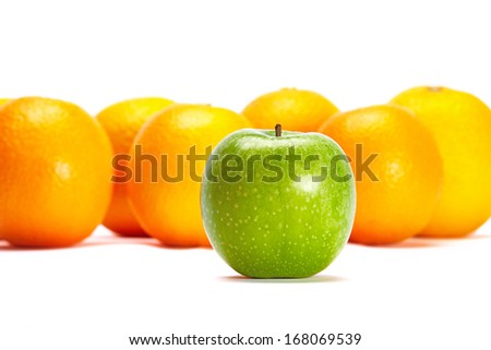 Green Apple In Front Of Oranges Conceptual Idea of Individuality - standing out of the crowd. - stock photo