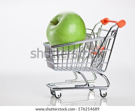 green apple in shopping carts on white background - stock photo