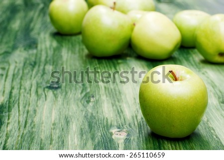 Green apple in the foreground, on a background scattering apples  - stock photo