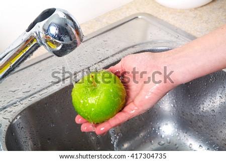 Green apple in the sink. Fresh apple - stock photo