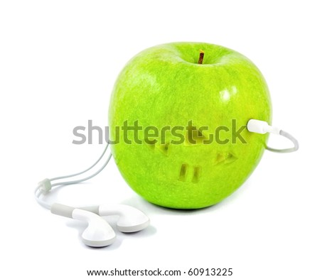 green apple in which headphones are connected - stock photo