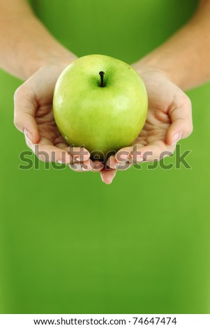 green apple in woman hands - stock photo