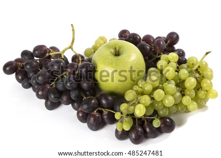 Green apple lies near a cluster of green and chyorony grapes on a white background.