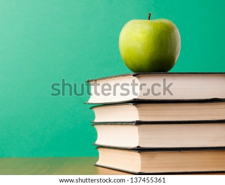 Green apple on a pile of books , isolated on green background - stock photo