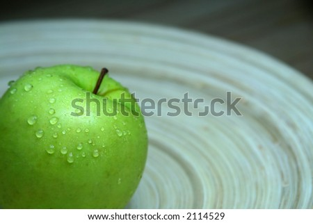 Green apple on a wooden tray with water droplets. Concept: Health. Shallow DOF. - stock photo