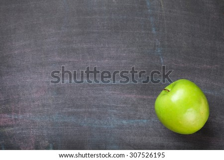 Green apple on blackboard or chalkboard background. Top view with copy space - stock photo
