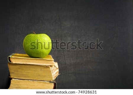 Green apple on old textbook against blackboard with copyspace - stock photo