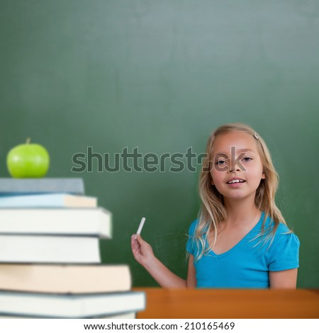 Green apple on pile of books against cute pupil holding chalk