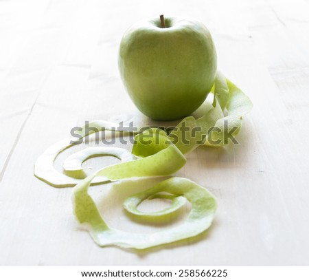 Green apple on rustic white table - stock photo