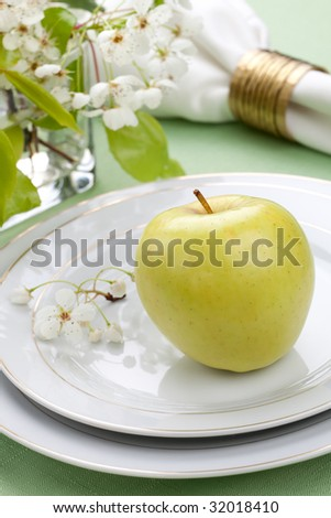 Green apple on spring table settings with fresh apple blossom twig
