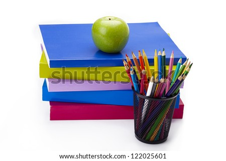 Green apple on stack of colorful books and a set of coloring pencil sitting in a basket.