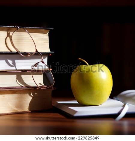 green apple on the open book with books and glass - stock photo