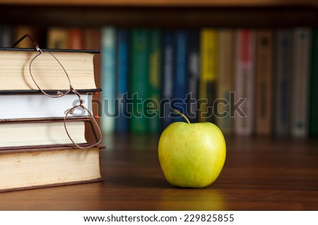 green apple on the table with books and glasses - stock photo