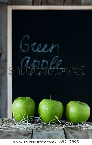 Green apple on the wooden table and chalk board background, selective focus - stock photo