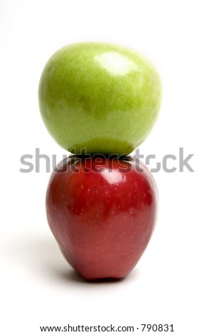 Green apple on top of the red one - stock photo