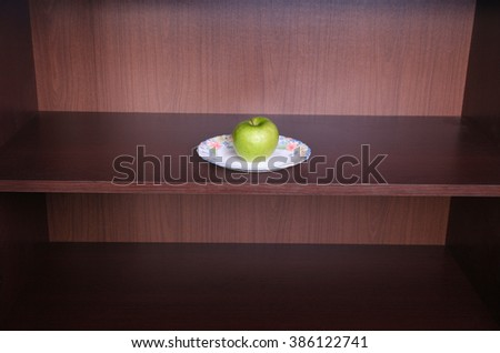 Green apple on white plate in the dark.