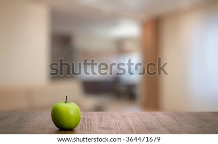 green apple on wooden table in the living room - stock photo