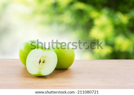 Green apple on wooden vintage table over bokeh background - stock photo
