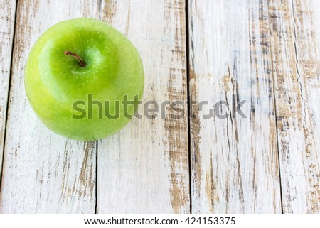 Green apple on wooden white background, top view