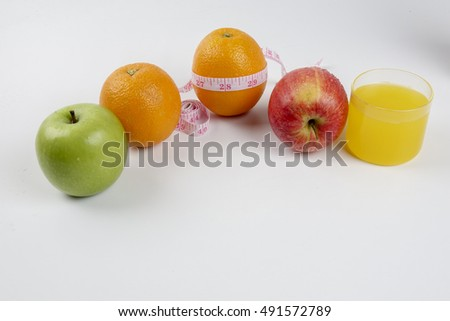 Green apple, red apple ,yellow orange and measuring tape. Diet concept