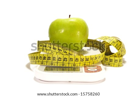 Green apple, scale and tape measure isolated