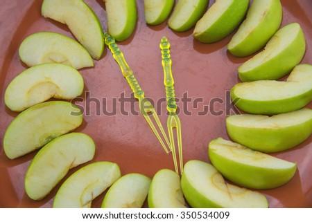 Green apple slice on orange plate. - stock photo