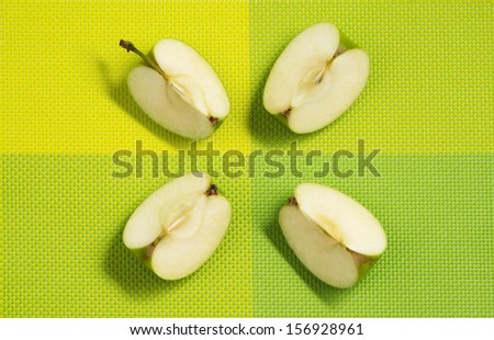 green apple slices on green tablecloth - stock photo