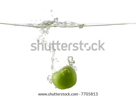 Green apple splashing in water on pure white - stock photo