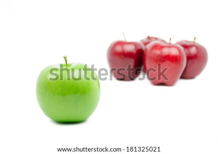 Green apple standing out from group of red apples on white background  - studio lighting.