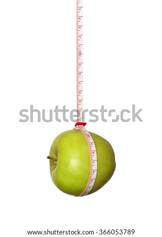 Green apple suspended on a measuring tape - stock photo