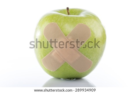 Green apple with a band-aid on white background - stock photo
