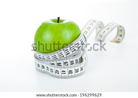 green apple with a ruler on a white background