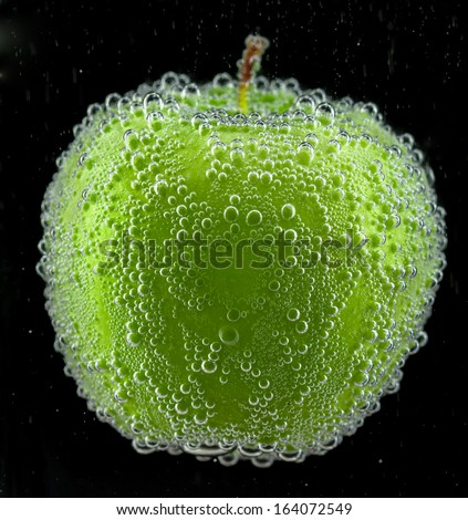 Green apple with bubbles on the black background - stock photo