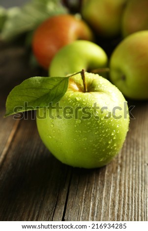 Green apple with leaf on brown wooden background - stock photo