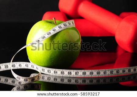 green apple with measure tape and red dumbbells for fitness - stock photo
