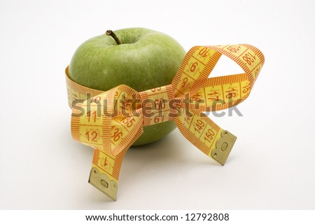 Green Apple with measuring tape. - stock photo