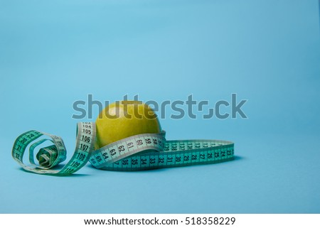 Green apple with measuring tape on blue background