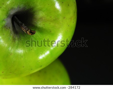 green apple with reflection on a mirror.