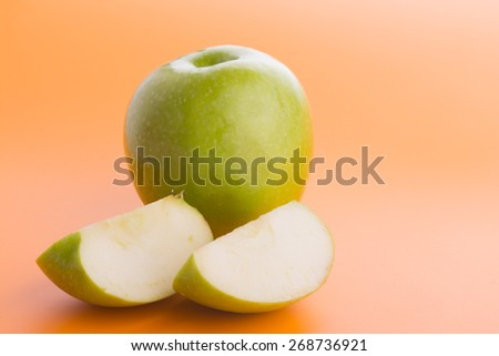 Green apple with slices on gradient orange background - stock photo