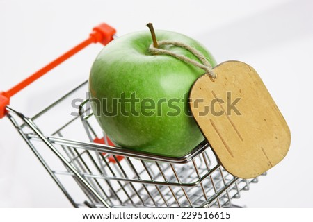 green apple with tag in shopping carts on white background - stock photo