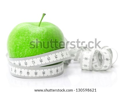 Green apple with tape measure isolated on white