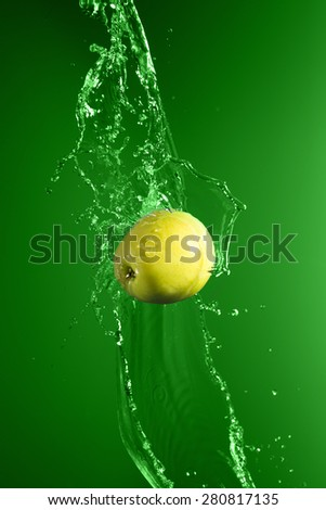 Green apple with water splash on green background - stock photo