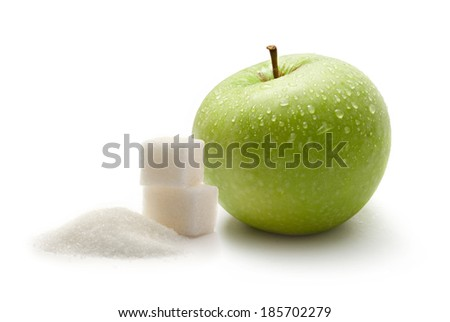 Green apple with white sugar cubes - stock photo