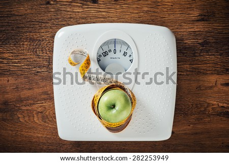 Green apple wrapped in a tape measure on a white scale, wooden surface on background, dieting and weight loss concept - stock photo