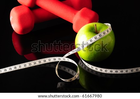 green apple wrapped with white measure tape and red dumbbells for fitness