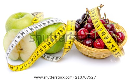 Green apples and a basket of cherries surrounded with a tape measure, isolated on white - stock photo