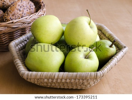 Green apples and bread rolls in a basket on table.  - stock photo