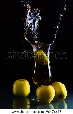 green apples and glass with juice on  dark background.