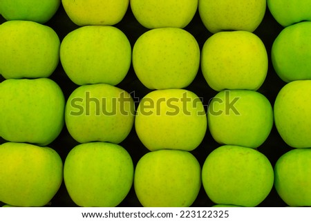 Green apples arranged in rows on table